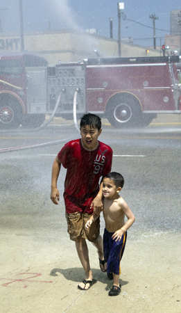 boys playing in the spray of a fire truck