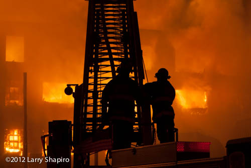 large fire scene silhouetted firefighters