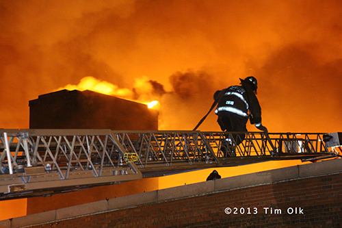 firefighter on ladder with fire