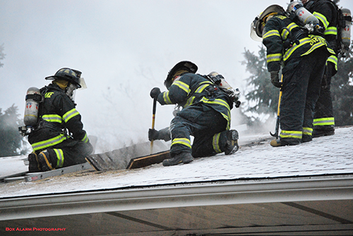 firefighters opening a roof