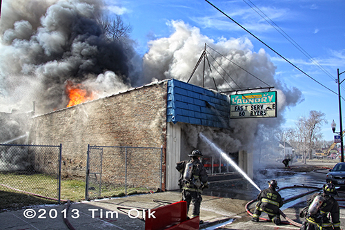 firefighters with hose line at big fire