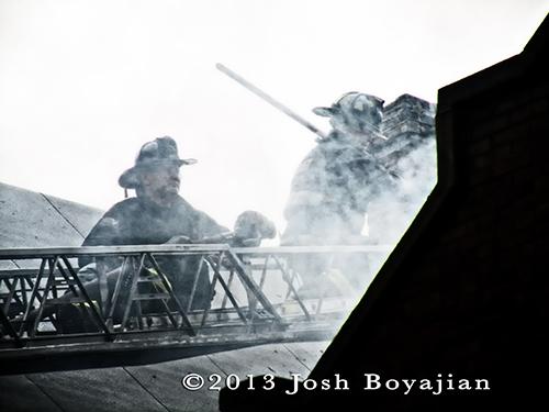 firemen on ladder with smoke