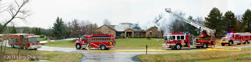 panorama of fire trucks at house fire