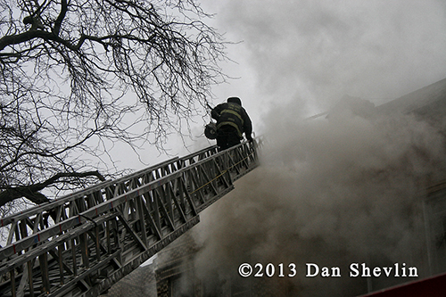 fireman climbs ladder into smoke