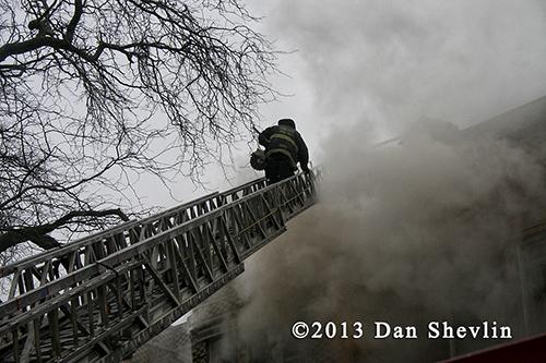 fireman climbs ladder into smoke