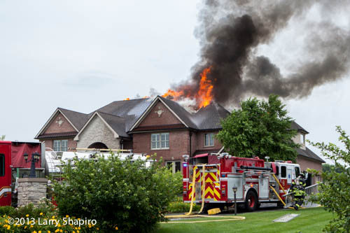 fire blows out the roof of a house