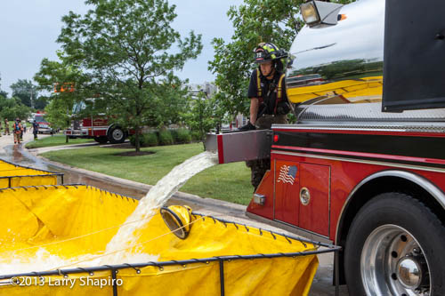 fireman dumps water from fire department water tanker