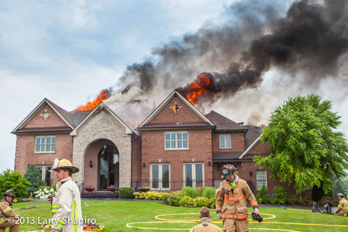massive house on fire with flames through the roof
