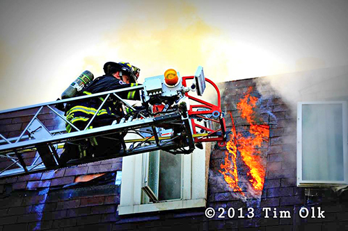 Firemen Working From Aerial Ladder