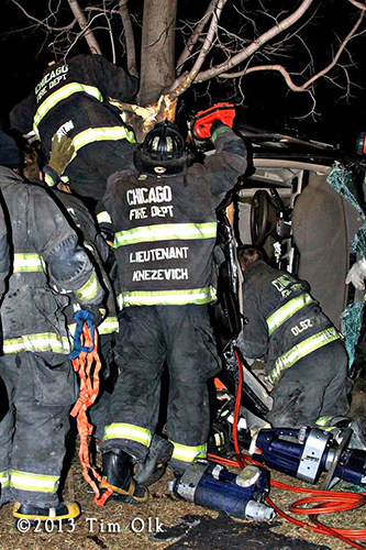 Chicago firefighters work to extricate a father and daughter from a one-car crash on Christmas eve