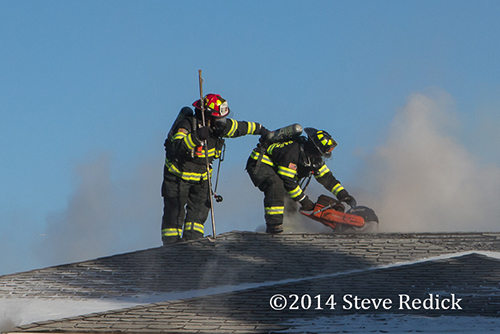 firemen use saw to ventilate roof at house fire