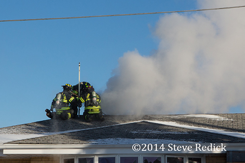firemen ventilate roof at house fire