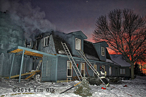 firemen at winter house fire at dusk