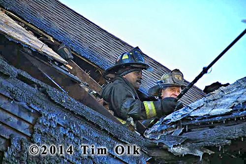 firemen overhaul fire scene from attic