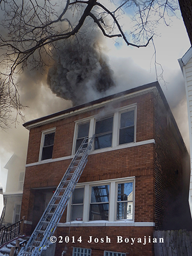 heavy smoke pushes from the attic of a Chicago two-flat