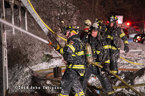 firemen covered with ice using a hose line
