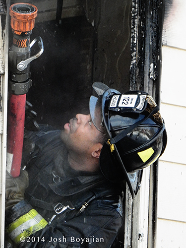 firefighter with hose at fire scene