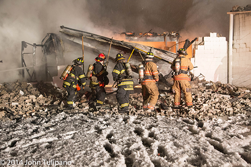 firemen overhaul warehouse fire