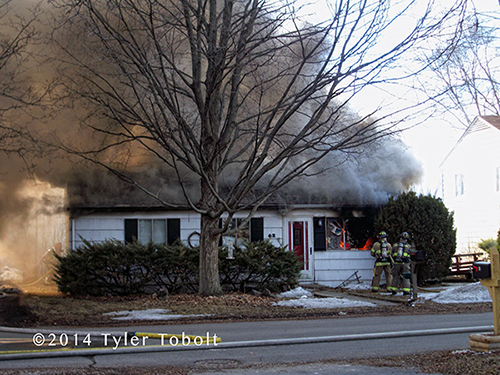 small house on fire with heavy smoke