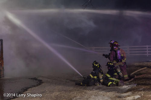 firemen with hose lines at winter fire scene
