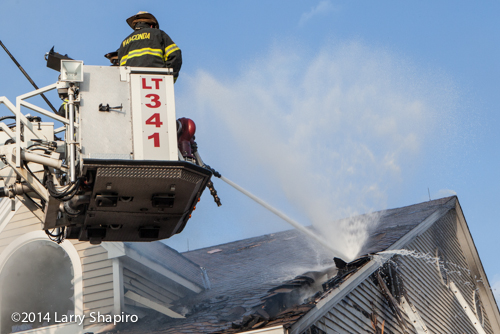 fireman uses master stream from tower ladder