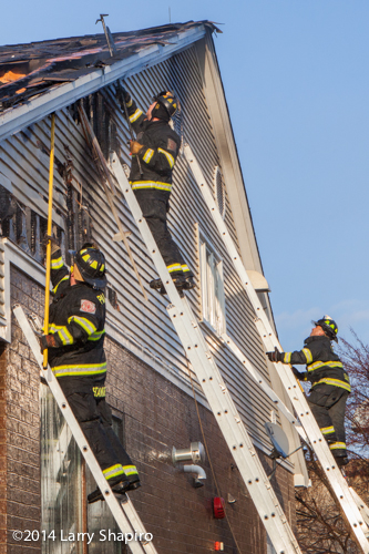 firemen working on ladders at fire scene