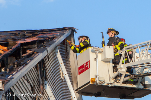 firemen overhaul from Pierce tower ladder