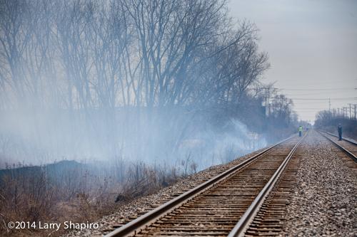smoke from grass fire along railroad tracks
