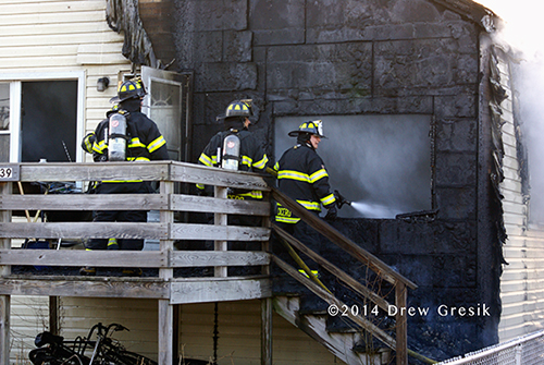 firemen with hose at house fire