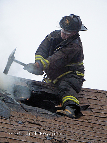 fireman using axe on a peaked roof