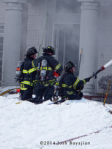 firemen with hose line at winter fire scene