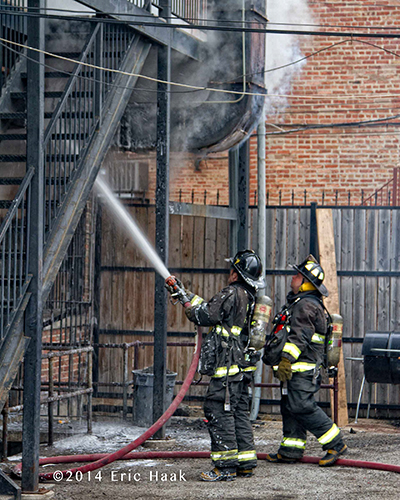 firemen with hose at restaurant fire