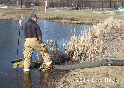 fireman supervises drafting water from a pond