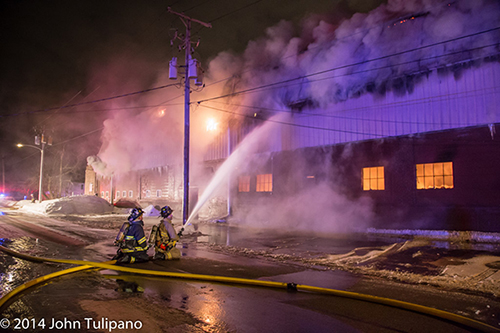 firemen with hose at huge industrial fire