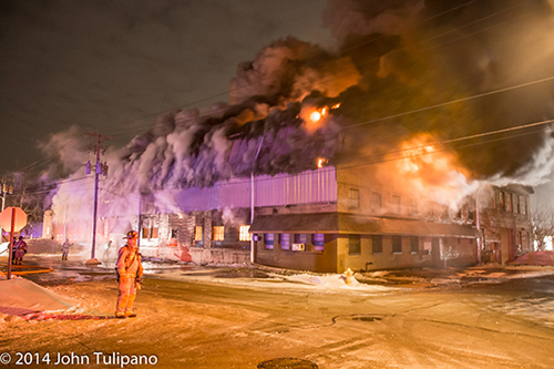 firemen at huge night time fire scene