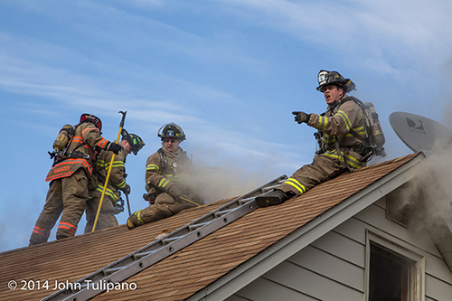 firemen on roof at house fire