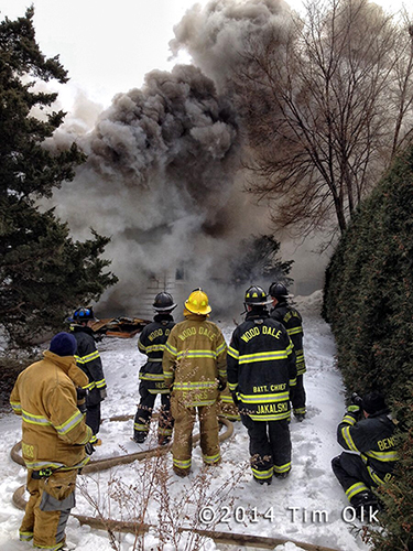 firemen at fire scene with heavy smoke