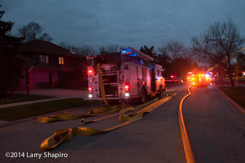 fire trucks with hose off at fire scene at dusk