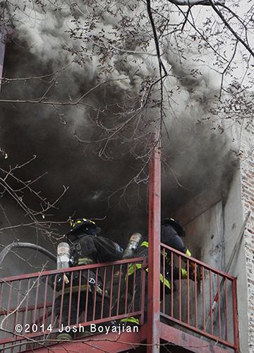 firemen make entry with heavy smoke overhead