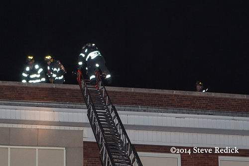 firemen climb ladder to the roof at night