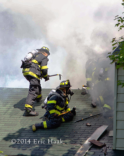 firemen working on the roof at house fire with heavy smoke