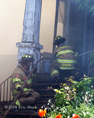 firemen with hose line at door of house