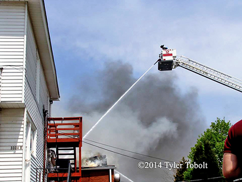 tower ladder with master stream at fire scene