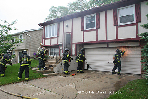 firemen use a saw to cut a garage door