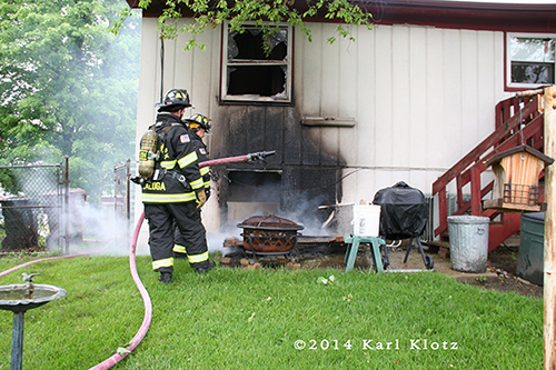 fireman with hose and charred siding