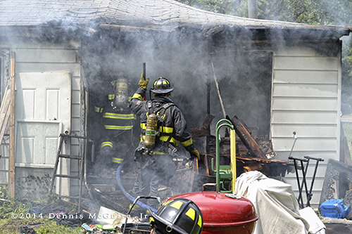 firemen working at a house fire scene
