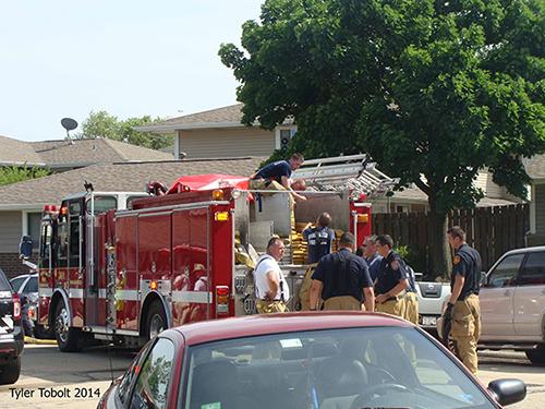 firemen pack hose on fire engine