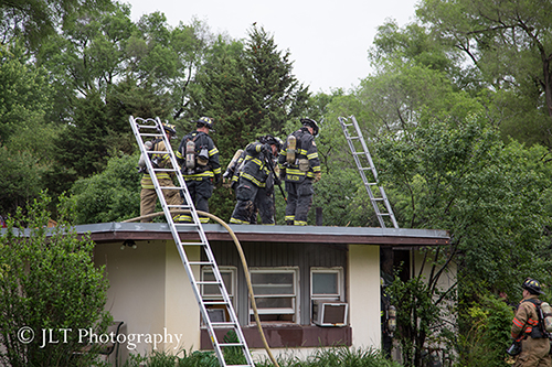 firemen on the roof of a house after fire