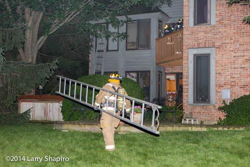 fireman carries ladder at night