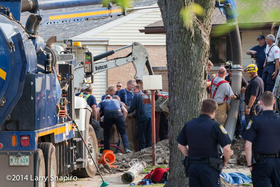 firemen use a sewer vac to rescue worker trapped in a trench